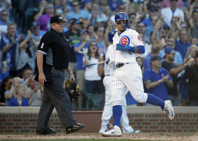 Chicago Cubs' Javier Baez, right, scores a run in front of umpire Bruce Dreckman (1) during the sixth inning of a baseball game against the Cincinnati Reds in Chicago, on Saturday, Sept. 15, 2018. (AP Photo/Jeff Haynes)