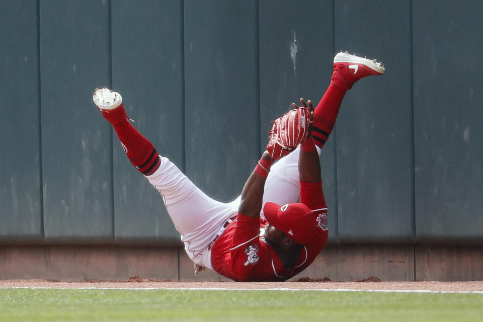 Cincinnati Reds right fielder Yasiel Puig lands after making a leaping catch against Miami Marlins' Curtis Granderson in the first inning of a baseball game, Thursday, April 11, 2019, in Cincinnati. (AP Photo/John Minchillo)