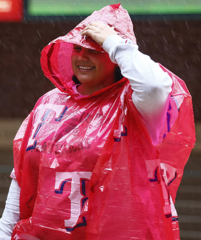 A fan waits out a rain delay before a baseball game between the Oakland Athletics and the Texas Rangers, Saturday, April 13, 2019, in Arlington, Texas. The Rangers delayed the start time of Saturday's game due to inclement weather. (AP Photo/Sam Hodde)