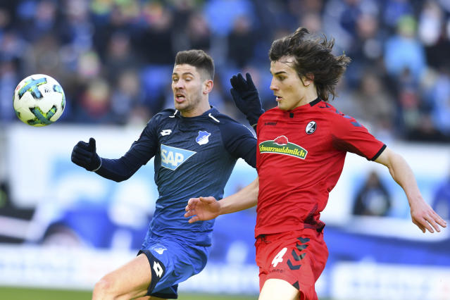 Hoffenheim's Andrej Kramaric, left, and Freiburg's Caglar Soyuncu challenge for the ball during the German Bundesliga soccer match between 1899 Hoffenheim and SC Freiburg in Sinsheim, southern Germany, Saturday, Feb. 24, 2018. (Uwe Anspach/dpa via AP)
