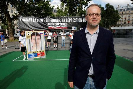 Christophe Deloire, director of Reporters Without Borders (RSF) poses next to giant portraits of seven imprisoned Russian journalists on Place de la Republique, transformed into a soccer field to denounce abuse of press freedom in Russia before the start of the 2018 FIFA World Cup Russia, in Paris, France, June 13, 2018.  REUTERS/Philippe Wojazer
