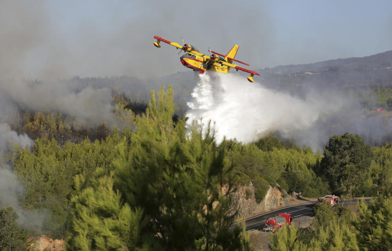 A firefighting airplane drops its load next to firetrucks on a road outside the village of Charneca, in the Sintra national park, west of Lisbon, Sunday, Oct. 7, 2018. Over 700 firefighters were battling a forest fire that started overnight about 40 kilometers (25 miles) west of Lisbon. (AP Photo/Armando Franca)