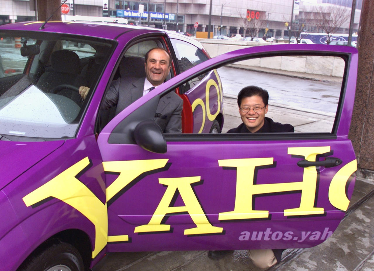 FORD AND YAHOO EXECUTIVES POSE WITH FORD PAINTED IN YAHOO SCHEME.