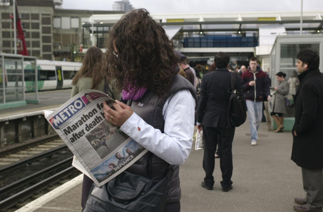 A commuter reads a newspaper featuring the Boston marathon bomb blasts on the front page, while waiting for a train at East Croydon station in south London, Tuesday, April 16, 2013. British police are reviewing security plans for Sunday's London Marathon, the next major international marathon, because of the bombs that killed three people at the marathon in Boston Monday. (AP Photo/Sang Tan)