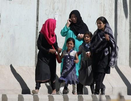 An Afghan family walk out from the site of a blast in Kabul, Afghanistan
