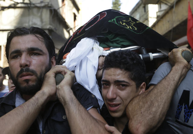 Lebanese Shiite mourners carry the body of Hamad al-Mekdad, 42, who was killed on Thursday by a car bomb explosion, during his funeral procession at an predominantly Shiite area and stronghold of the Lebanese militant group Hezbollah in the southern suburb of Beirut, Lebanon, Friday, Aug. 16, 2013. Lebanese forensic experts collected evidence Friday at the scene of a massive explosion in a southern suburb of Beirut that killed dozens of people and wounded hundreds, the deadliest blast in the area in nearly three decades. (AP Photo/Hussein Malla)