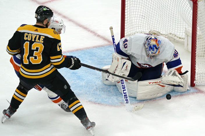 New York Islanders goaltender Semyon Varlamov (40) keeps the puck in front as Boston Bruins center Charlie Coyle (13) is defended by Islanders center Mathew Barzal during the third period of Game 5 of an NHL hockey second-round playoff series, Monday, June 7, 2021, in Boston. (AP Photo/Elise Amendola)
