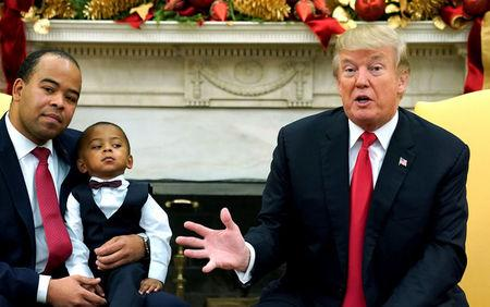Aaron Williams of Indianapolis, with his son on his lap, listens as U.S. President Donald Trump holds a discussion with business owners and their families in the Oval Office of the White House in Washington, U.S., December 5, 2017.  REUTERS/Kevin Lamarque