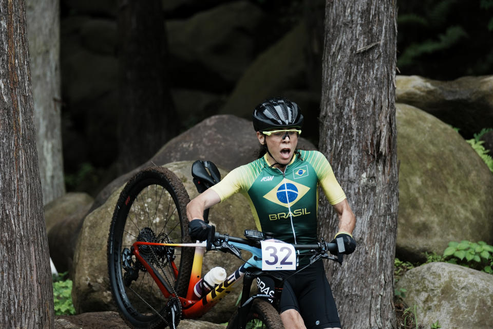 Jaqueline Mourao of Brazilcarries her bike over rocks during the women's cross-country mountain bike competition at the 2020 Summer Olympics, Tuesday, July 27, 2021, in Izu, Japan. (AP Photo/Thibault Camus)