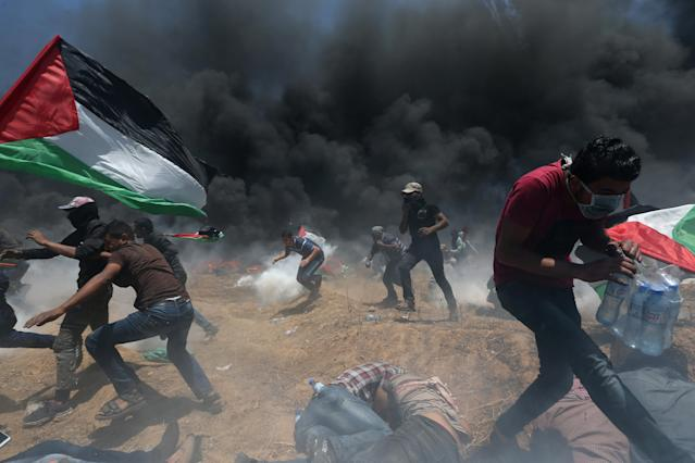 <p>Palestinian demonstrators run for cover from Israeli fire and tear gas during a protest against the U.S. Embassy's move to Jerusalem, at the Israel-Gaza border in the southern Gaza Strip, May 14, 2018. (Photo: Ibraheem Abu Mustafa/Reuters) </p>