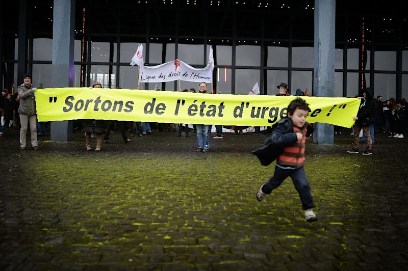 "A child runs as people hold a banner reading ""Let's end the state of emergency"" during a demonstration on January 30, 2015 in Nantes (AFP Photo/Jean-Sebastien Evrard)"