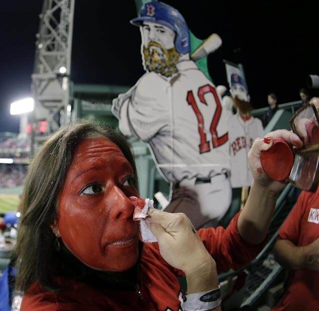 Krista Provencal puts on red makeup in Fenway Park before Game 1 of baseball's World Series between the Boston Red Sox and the St. Louis Cardinals Wednesday, Oct. 23, 2013, in Boston. (AP Photo/Charlie Riedel)