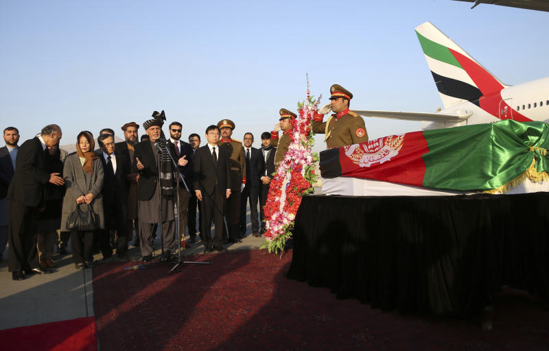 Afghan President Ashraf Ghani, speaks, next to the coffin of Japanese physician Tetsu Nakamura during a ceremony before transporting his body to his homeland, at the Hamid Karzai International Airport in Kabul, Afghanistan, Saturday, Dec. 7, 2019. Nakamura was killed earlier this week in a roadside shooting in eastern Afghanistan. (AP Photo/Rahmat Gul)