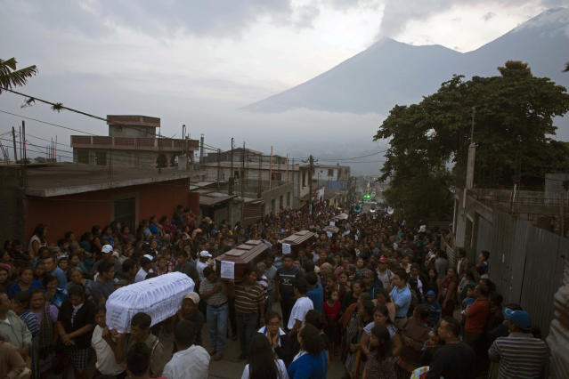 <p>People carry the coffins of seven people who died during the eruption of the Volcan de Fuego, which in Spanish means Volcano of Fire, in the background, to the cemetery in San Juan Alotenango, Guatemala, Monday, June 4, 2018. (Photo: Luis Soto/AP) </p>