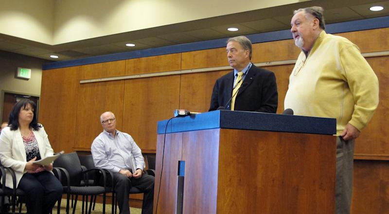 Fargo Mayor Dennis Walaker, in yellow sweater, and Deputy Mayor Tim Mahoney stand at the podium and talk about the city's flood fighting plans with city engineer April Walker and City Administrator Pat Zavoral looking on Thursday, March 21, 2013. The National Weather Service said Thursday, March 21, 2013 thet Fargo and neighboring Moorhead, Minn., residents should prepare for one of the top five floods in their history. (AP Photo/Dave Kolpack)