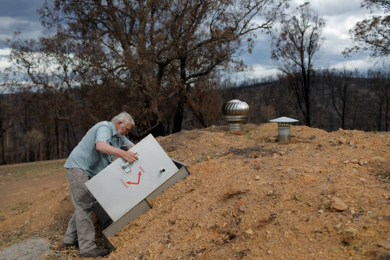 Donald Graham, 68, displays his bunker that he and his wife Bron took shelter in as their home was destroyed by bushfire in Buchan, Victoria, Australia