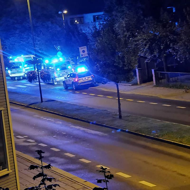 Police and emergency services are parked at the side of the road after people were stabbed in several locations in Sarpsborg