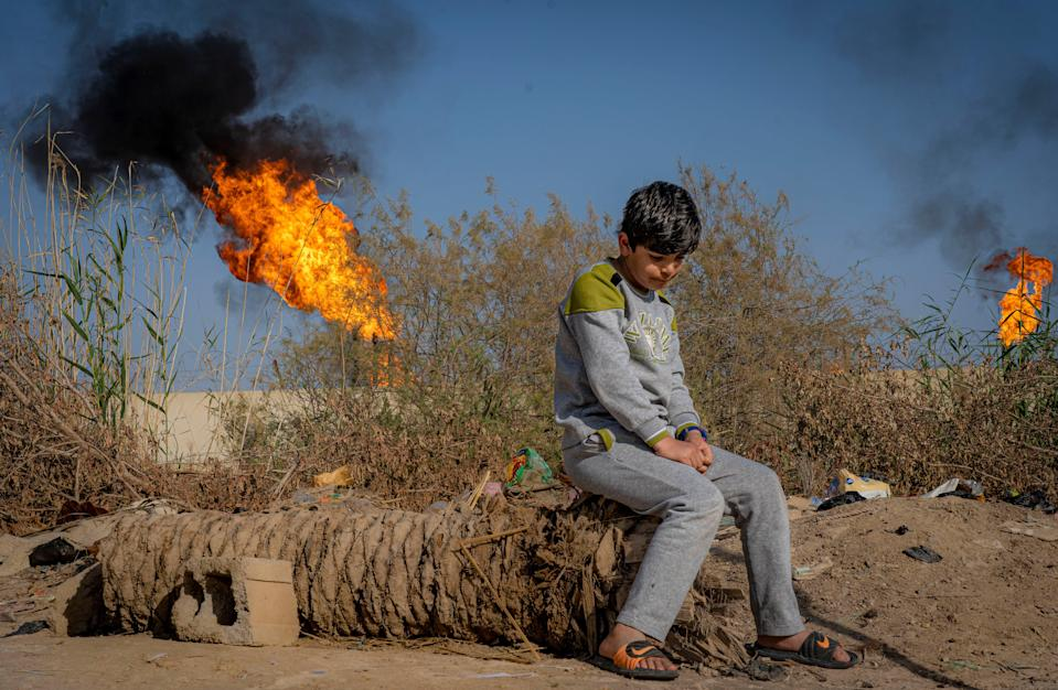 A young boy sits in front of the toxic chimneys of a gas flare in Nahran Omar, southern IraqBel Trew