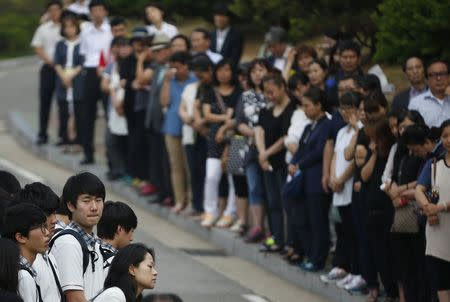 Students who survived the April 16 ferry disaster gather at the main gate as they make their way back to school in Ansan