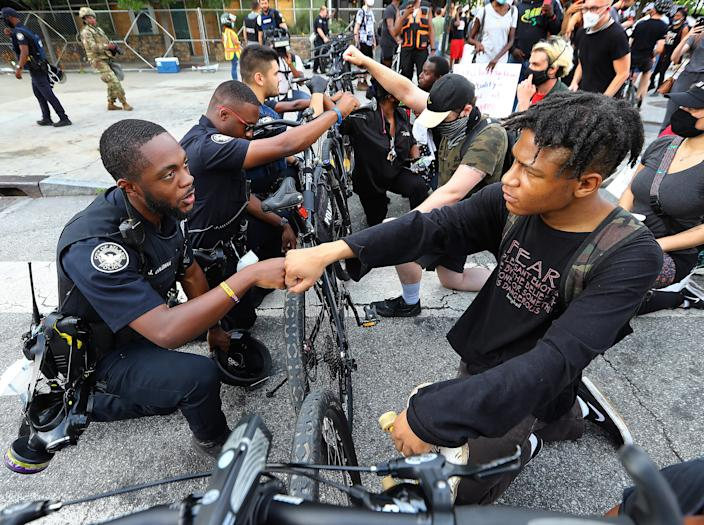 Police officers and protesters fist-bumping in a symbolic gesture of solidarity outside the CNN Center on June 3 in Atlanta.