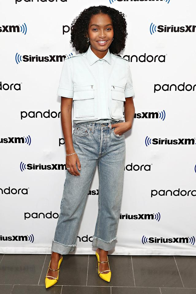 in a light blue collared blouse with zipper details and pockets, paired with light wash straight-leg jeans and yellow pumps at SiriusXM Studios in N.Y.C.