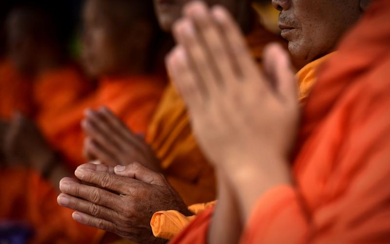 Monks attend a Buddhist prayer for the missing children near Tham Luang cave - AFP