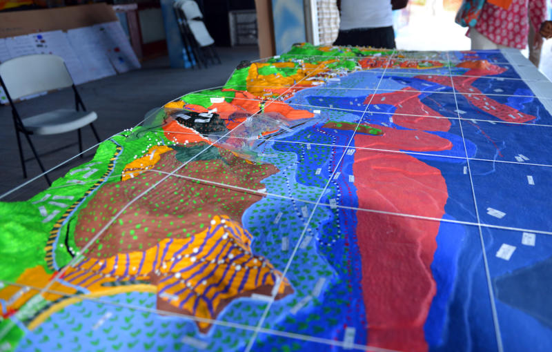 In this April 22, 2013 photo, a model showing the impact of coastal erosion on eastern communities in Grenada is on display at a community center in Grenville, Grenada. The people along this vulnerable stretch of eastern Grenada have been watching the sea eat away at their shoreline in recent decades, a result of destructive practices such as sand mining and a ferocious storm surge made worse by climate change, according to researchers with the U.S.-based Nature Conservancy, who have helped locals map the extent of coastal erosion. (AP Photo/David McFadden)