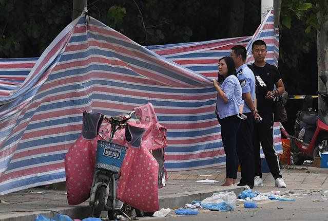 <p>Police officers peer over a screen placed outside a kindergarten where an explosion killed 8 people and injured dozens a day earlier, in Fengxian, in China's eastern Jiangsu province on June 16, 2017. (Photo: Greg Baker/AFP/Getty Images) </p>