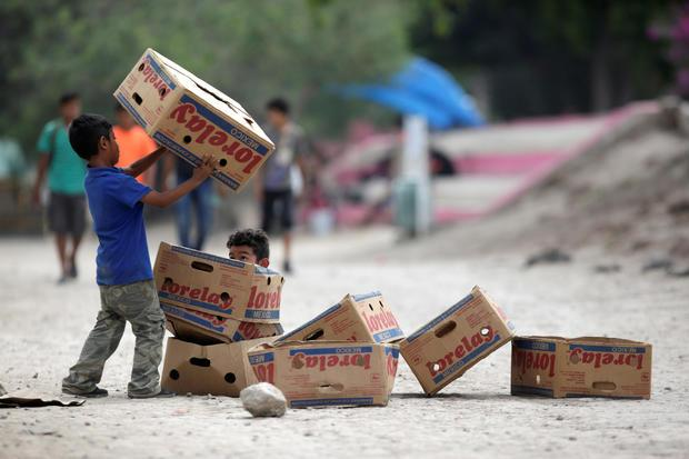 Migrant children play with cardboard boxes at a migrant encampment where more than 2,000 people live while seeking asylum in the U.S., while the spread of Coronavirus disease (COVID-19) continues, in Matamoros