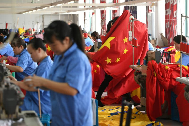 FILE PHOTO: Workers make Chinese flags at a factory ahead of the 70th founding anniversary of People's Republic of China, in Jiaxing, Zhejiang