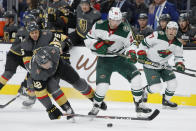 Vegas Golden Knights left wing Tomas Nosek (92) and Minnesota Wild left wing Kevin Fiala (22) vie for the puck during the second period of an NHL hockey game Tuesday, Dec. 17, 2019, in Las Vegas. (AP Photo/John Locher)