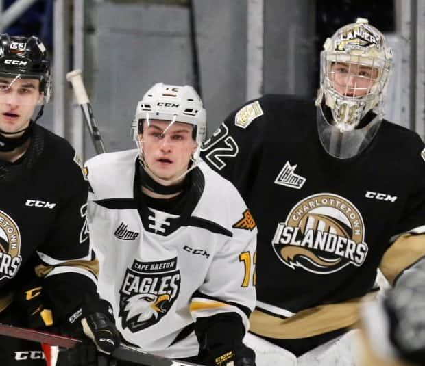 Charlottetown Islanders goaltender Colten Ellis, right, looks around Cape Breton Eagles forward Jack Campbell and Islanders defenceman Sean Stewart earlier this month at Centre 200 in Sydney, N.S. A game between the two teams on Sunday was cancelled due to illness. (Mike Sullivan - image credit)
