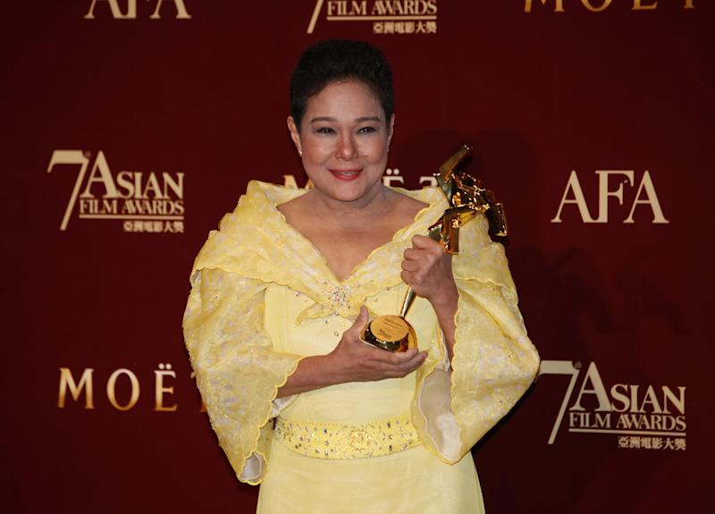 """The Philippines actress Nora Aunor poses with her trophy after winning the Best Actress Award of her movie """"Thy Womb"""" at the Asian Film Awards as part of the 37th Hong Kong International Film Festival in Hong Kong Monday, March. 18, 2013. (AP Photo/Kin Cheung)"""
