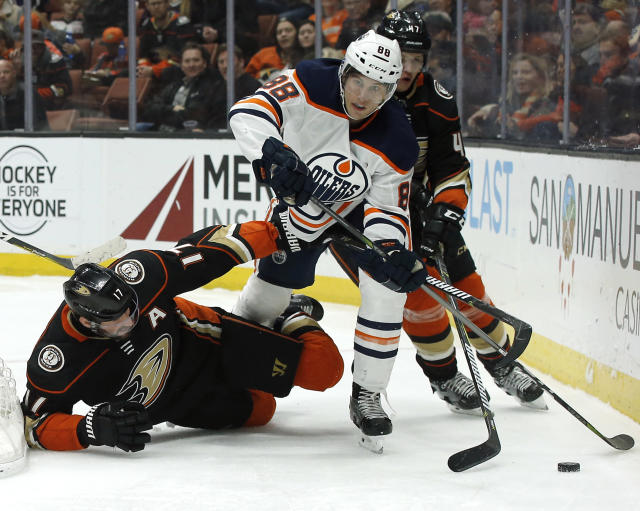Edmonton Oilers defenseman Brandon Davidson, center, steps over Anaheim Ducks center Ryan Kesler, left, to control the puck as defenseman Hampus Lindholm, of Sweden, trails during the second period of an NHL hockey game in Anaheim, Calif., Friday, Feb. 9, 2018. (AP Photo/Alex Gallardo)