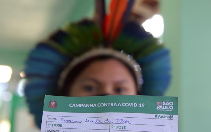 An Indigenous woman shows her vaccination card after receiving the second dose of Sinovac's CoronaVac vaccine at a health station, in Guarulhos, near Sao Paulo - Reuters