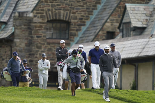 Dustin Johnson, second from right, walks down the 10th hole fairway during practice for the U.S. Open Championship golf tournament at Winged Foot Golf Club, Tuesday, Sept. 15, 2020, in Mamaroneck, N.Y. (AP Photo/John Minchillo)
