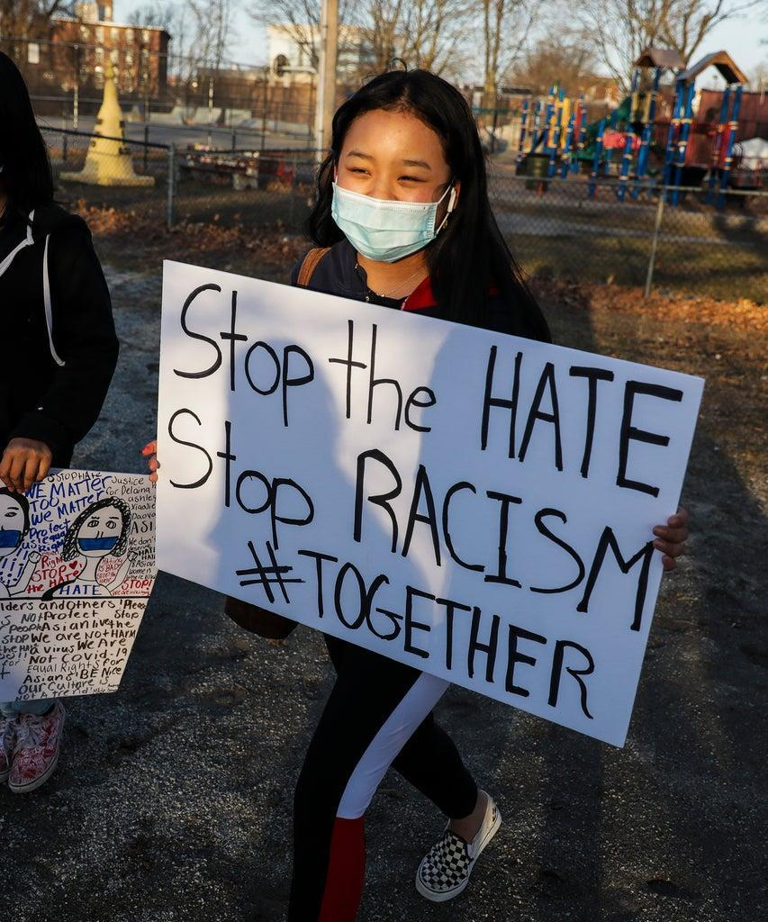 """LOWELL – MARCH 17: Children carry """"stop the hate"""" and """"Asian lives matter"""" as they walk around Clemente Park in Lowell, Mass. during a vigil held for the victims of the shooting spree in Atlanta at Clemente Park Lowell, MA on March 17, 2021. Eight people including six Asian women were killed in the massage parlor shootings. The event was hosted by the Cambodian Mutual Assistance Association. (Photo by Erin Clark/The Boston Globe via Getty Images)"""