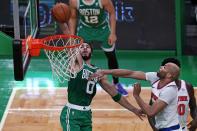 Boston Celtics forward Jayson Tatum (0) dunks after driving past New York Knicks center Taj Gibson, right, during the first half of an NBA basketball game Wednesday, April 7, 2021, in Boston. (AP Photo/Charles Krupa)