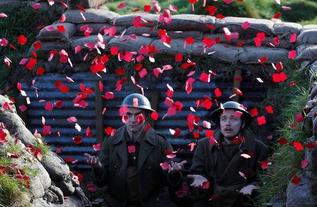 Actors Jake Morgan and Sam Ducane extend their hands to catch poppies, as they pose for photographs at the launch of the 1918 Poppy Pledge in a re-creation of a First World War trench at Pollock House in Glasgow, Scotland November 10, 2017. The actors appeared in the The Wipers Times, a play named after a magazine published by British soldiers in the First World War.  REUTERS/Russell Cheyne