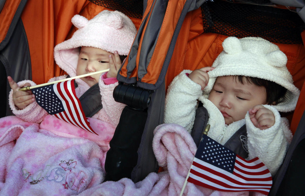 Rachel and Julia Song, 10 months old, of South Korea and New York City, attend a naturalization ceremony at the Statue of Liberty, Friday, Oct. 28, 2011 in New York. The oath of citizenship was taken by 125 people, to mark the Statues's 125th anniversary. Gryschenko is a corpsman with the U.S. Coast Guard. (AP Photo/Mark Lennihan)