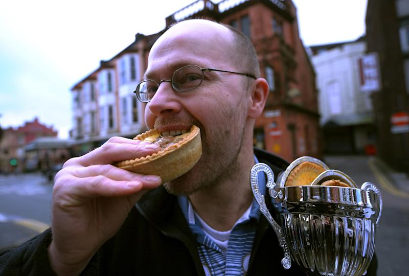 File photo for illustration shows a man eating a pie in Wigan, northern England, on December 15, 2009
