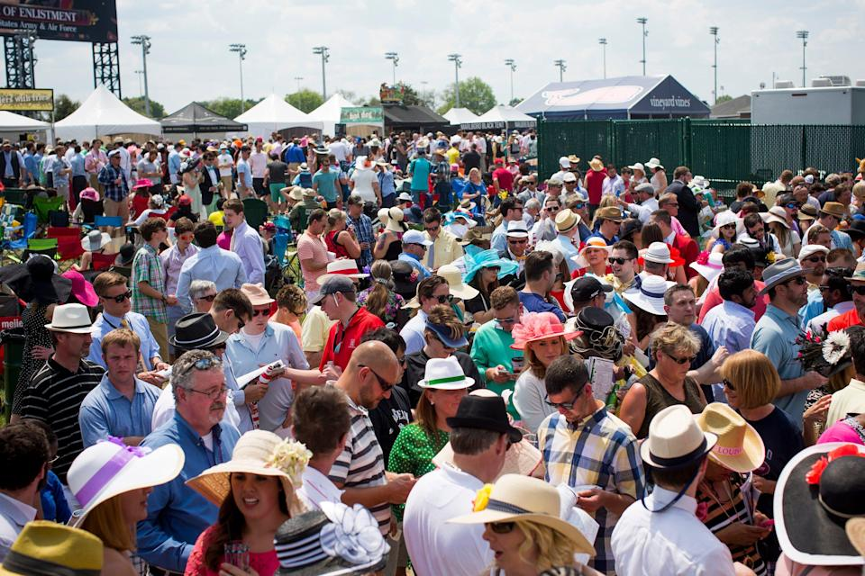A large crowd lined up in front of one of the infield betting stands at Churchill Downs.