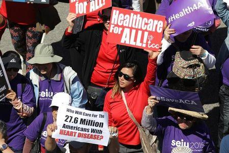 "People march in a ""Save Obamacare"" rally on the seventh anniversary of Obamacare's signing, in Los Angeles"
