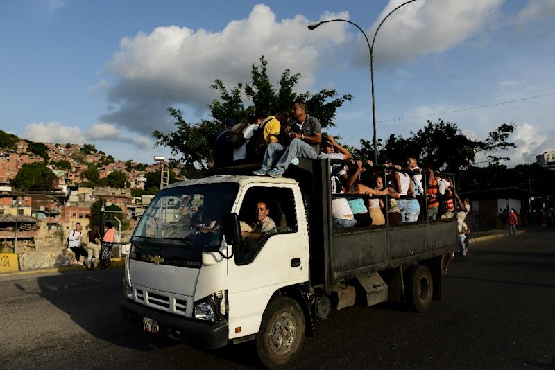 People ride on a truck turned bus in a Caracas slum -- one way to deal with a transport mess that is part of Venezuela's economic crisis (AFP Photo/Federico PARRA)