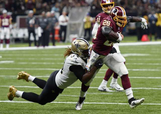 Washington Redskins running back Adrian Peterson (26) carries against New Orleans Saints defensive end Cameron Jordan (94) in the first half of an NFL football game in New Orleans, Monday, Oct. 8, 2018. (AP Photo/Bill Feig)