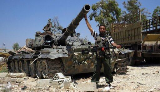 A Syrian rebel fighter poses in front of a tank reportedly taken from an army barracks, on June 14, 2013. There are rising international tensions over Western efforts to arm the rebels