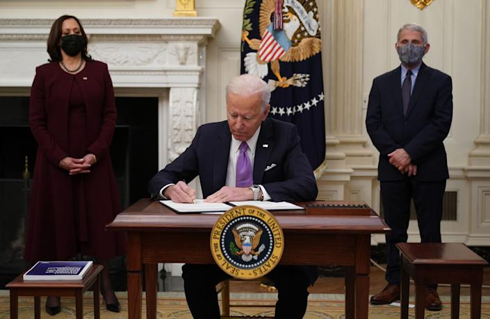 President Joe Biden signs executive orders on Jan. 21 as part of the COVID-19 response as Vice President Kamala Harris (left) and infections disease expert Dr. Anthony Fauci look on. (Photo: MANDEL NGAN via Getty Images)