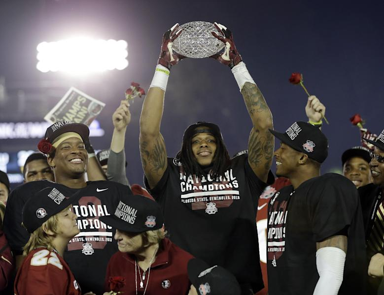 Florida State's P.J. Williams holds up his defensive player of the game trophy after the NCAA BCS National Championship college football game against Auburn Monday, Jan. 6, 2014, in Pasadena, Calif. Florida State won 34-31. (AP Photo/David J. Phillip)