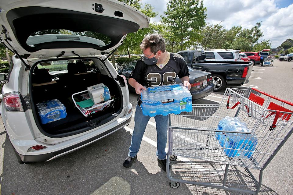 Tyler Anderson loads up water and other supplies at the Costco Sunday, Sept. 13, 2020, as New Orleans prepares for the arrival of what is expected to be Hurricane Sally.