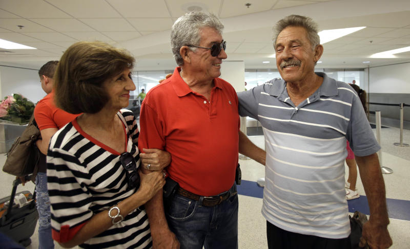 In this Sept. 11, 2013, photo, Benito Perez, right, smiles as he talks to his friends Rogelia Ventura, left, and Luis Ventura, center, at his arrival at Miami International Airport, in Miami. Perez, who had never been on a plane, is one of thousands of Cubans traveling under new laws making travel slightly easier. (AP Photo/Alan Diaz)